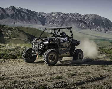 Person riding black Polaris utility vehicle